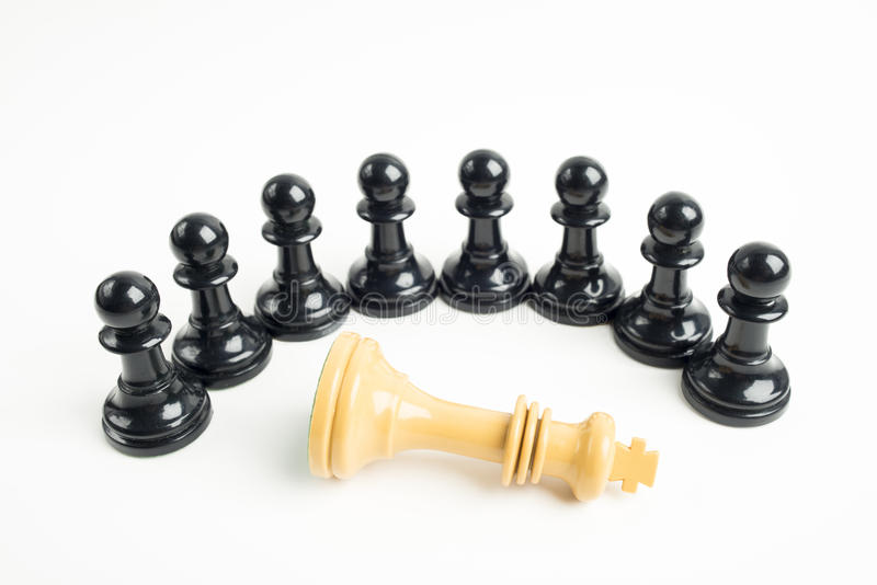 Black pawns around fallen white king stock images