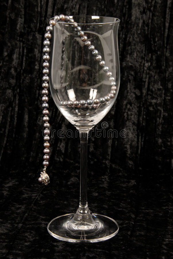 Black pearls in wine glass. stock photo