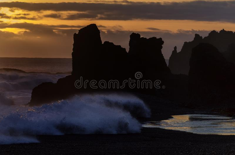 Black Pebbled Beach. Peculiar rock formations and crashing waves on the black pebbled beach at sunset, Djúpalónssandur, Iceland stock image