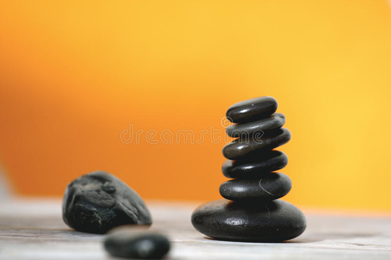 Black pebbles. Zen inspiration... six black stones on the table in orange background stock photos
