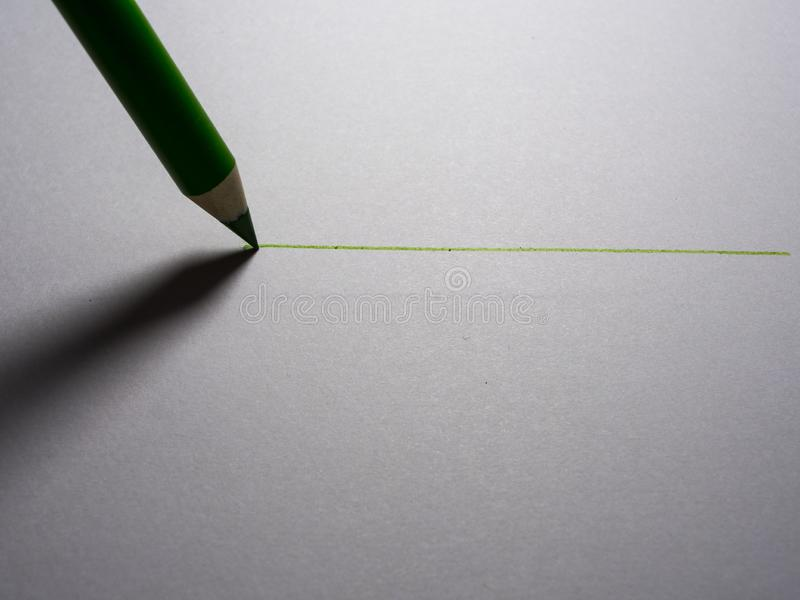 A black pencil draws a line on a white piece of paper. Concept, object, graphite, artistic, contrast, creative, ideas, shortened, two, equipment, celebrating royalty free stock photos