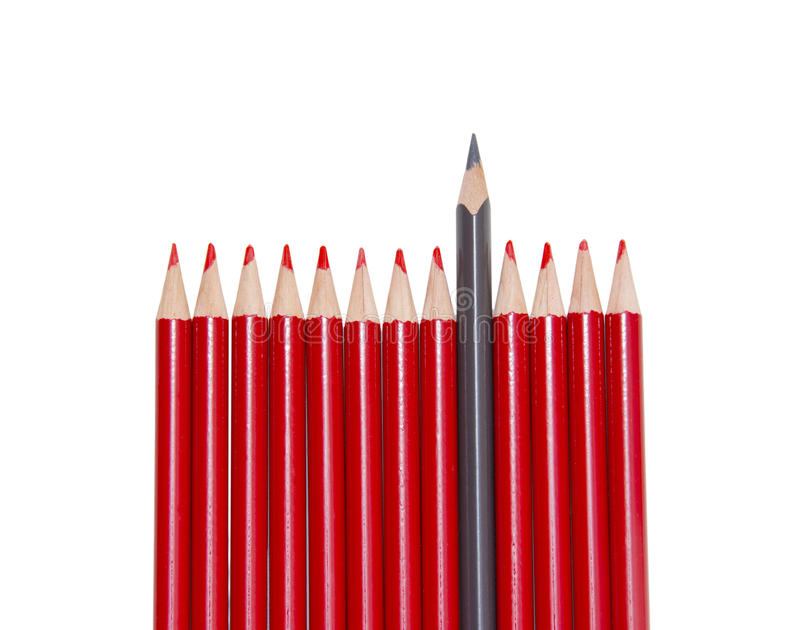 Black pencil standing out from the red pencils, isolated royalty free stock images