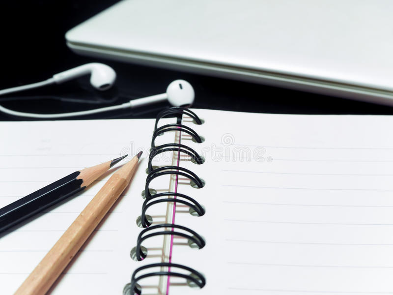 Black pencil and wooden pencil and book and laptop hoop on the teble royalty free stock photography