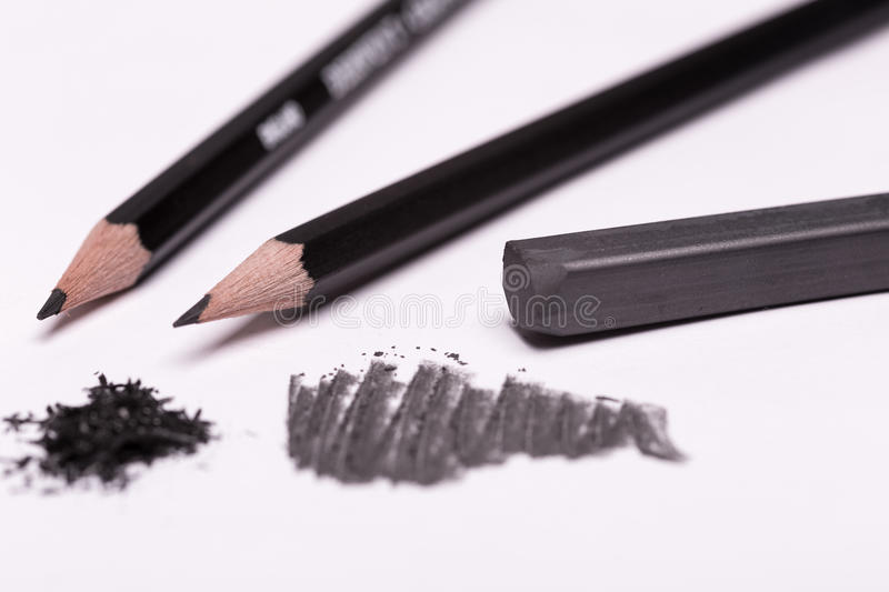 Black pencils and graphit. Few simple pencils and graphite and drawing on white background stock images
