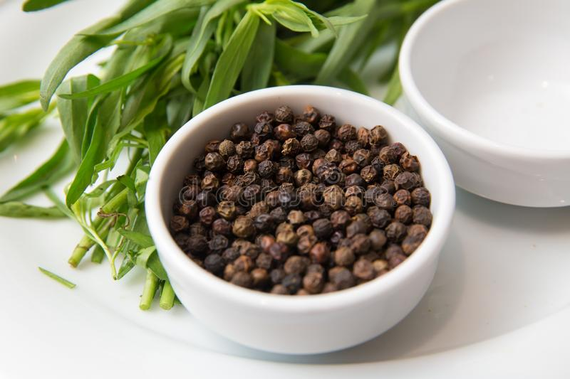 Black pepper in white bowl over white background . Saucer dish with black pepper peas isolated on white background . Dry black royalty free stock photos