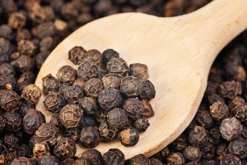 Black pepper on wooden spoon stock images