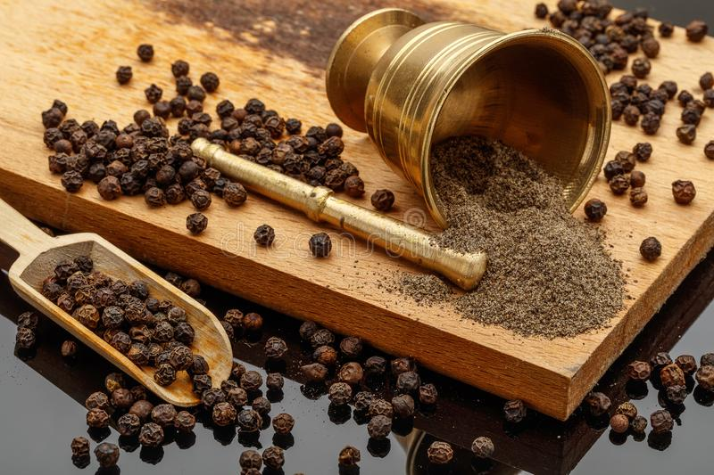 Black peppercorn and ground black pepper. On wood cutting board royalty free stock photography