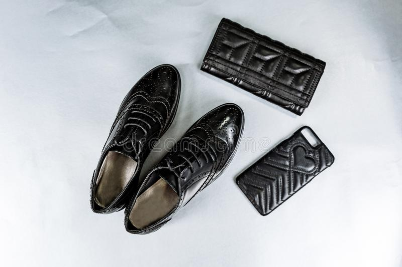 Black perforated shoes oxfords, a purse and a phone case on a paper white background royalty free stock photography