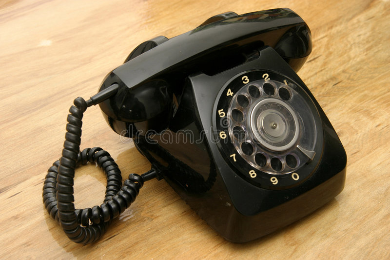 Black phone. Antique Ivory black dial phone with a bright wood-grain background royalty free stock images