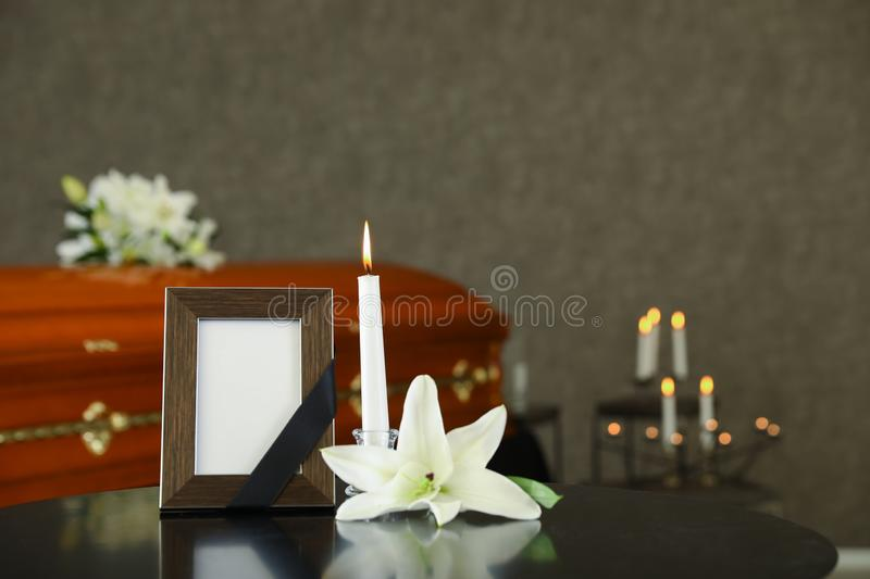 Black photo frame with burning candle and  lily on table in funeral home stock images