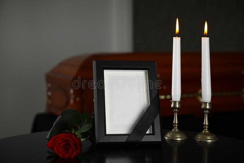 Black photo frame with  candles and red rose on table in funeral home stock image