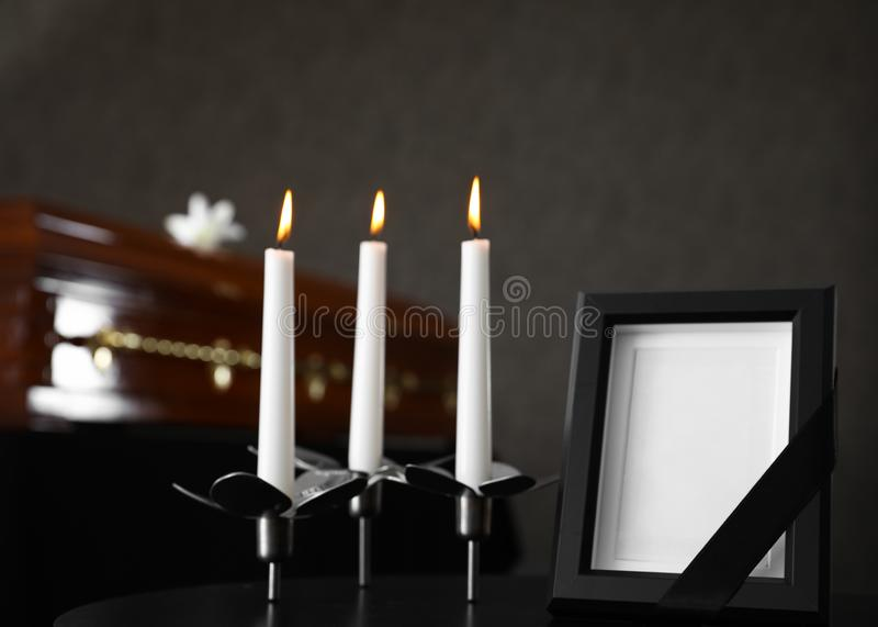 Black photo frame with candles on table in funeral home stock photo
