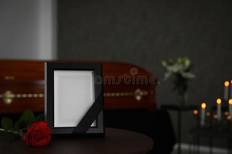 Black photo frame and red rose on  in funeral home royalty free stock image