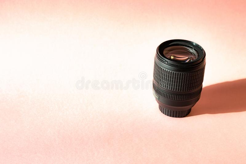 Black photo lens on pink background. Technology development hipster photographer hobby classic memory trip . stock photos
