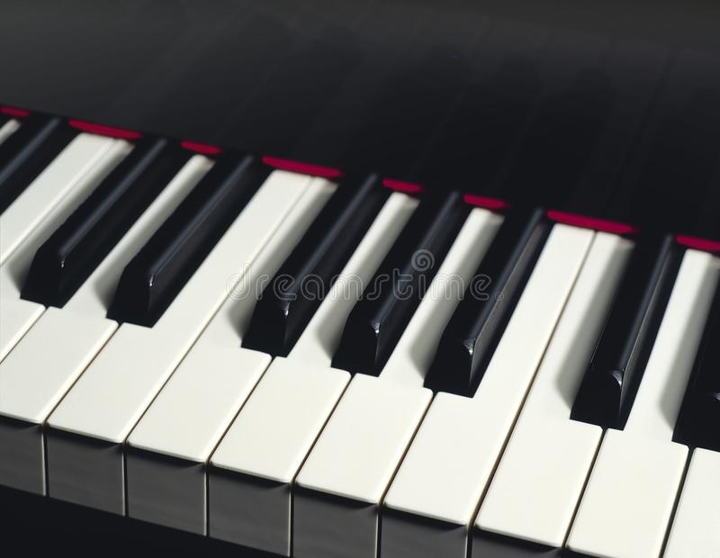 BLACK PIANO KEYS CLOSEUP. Black piano and keys in closeup with slight reflection in the black area above stock images