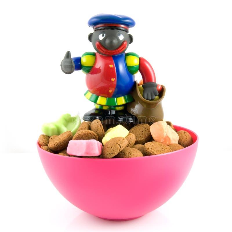 Black Piet on pink bowl with pepernoten royalty free stock photos