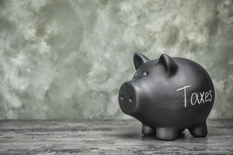 Black piggy bank with word TAXES. On table royalty free stock photos