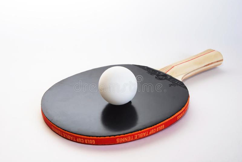 Black ping-pong paddle with the ball stock photography