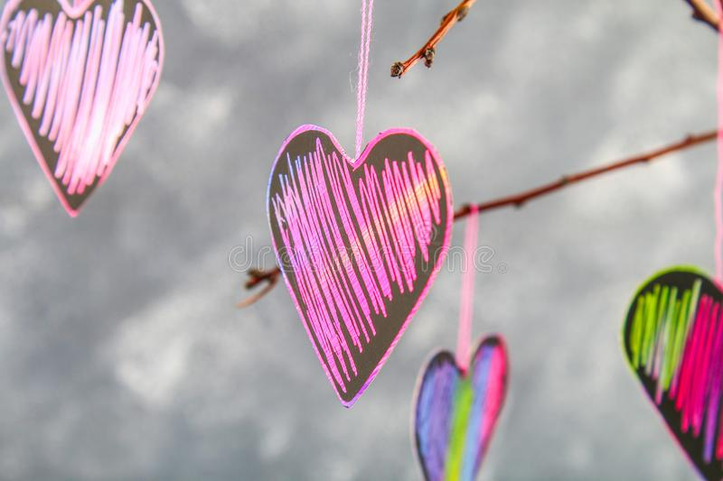 Black-pink hearts hang on branches on a gray concrete background. Love tree. The concept of Valentine's Day. A symbol of love. Black-pink hearts hang on royalty free stock photography
