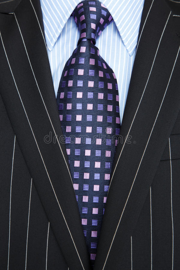 Black pinstripe suit and purple tie. Photo of a black pinstripe suit with blue striped shirt and purple and blue patterned tie royalty free stock photography