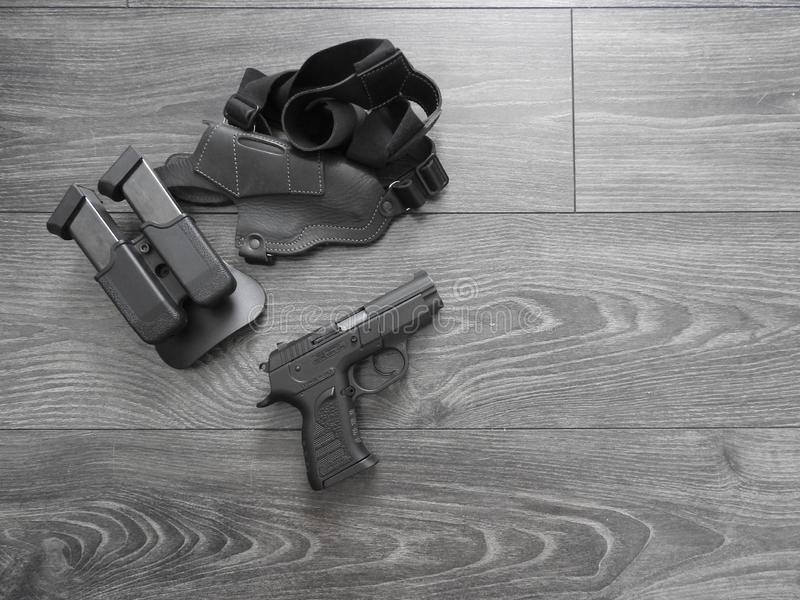 Black pistol in holster and magazines with weathered wood backdrop.  stock photo
