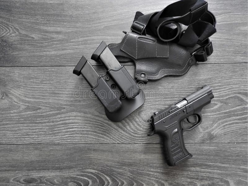 Black pistol in holster and magazines with weathered wood backdrop.  stock photography