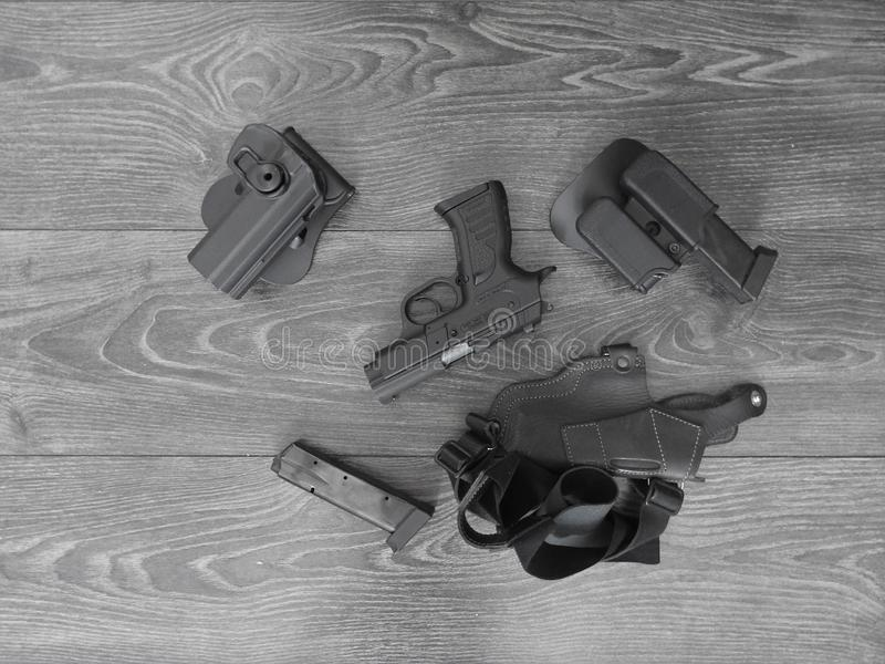 Black pistol in holster and magazines with weathered wood backdrop.  royalty free stock photography