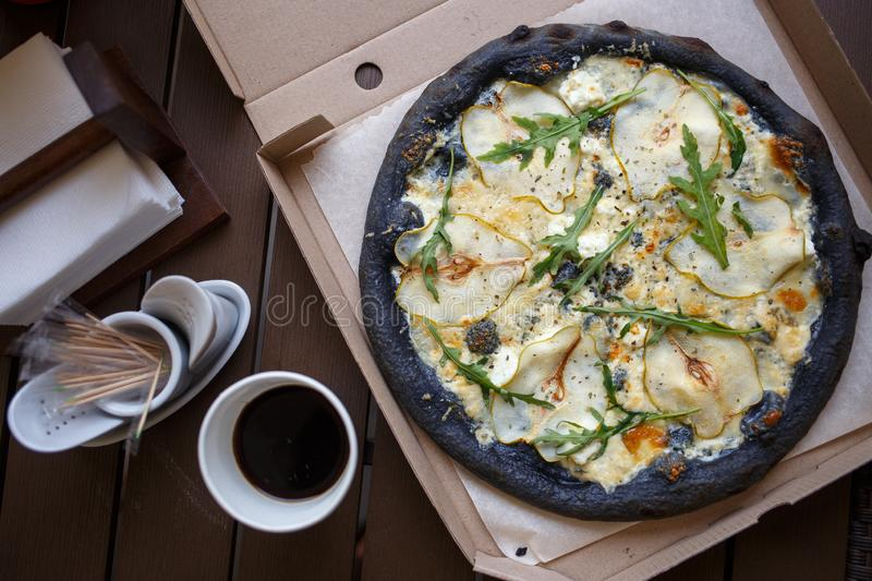 Black pizza four cheese with coffee top view image stock image