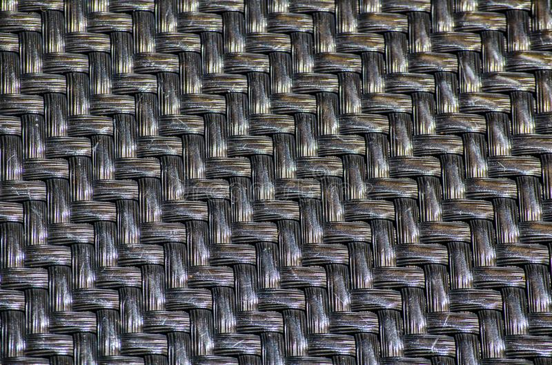 Black plastic basketwork pattern process of weaving or sewing pliable materials. A Black plastic basketwork pattern process of weaving or sewing pliable royalty free stock image