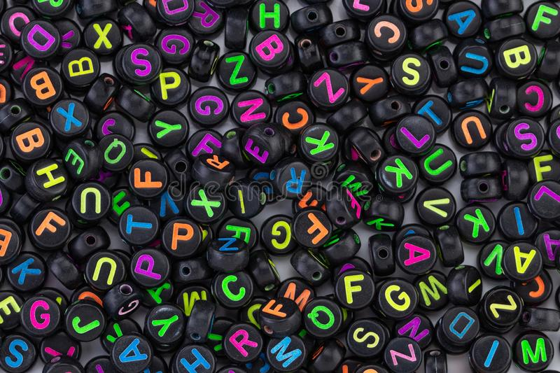 Black plastic beads with colored letters placed randomly.  stock photos