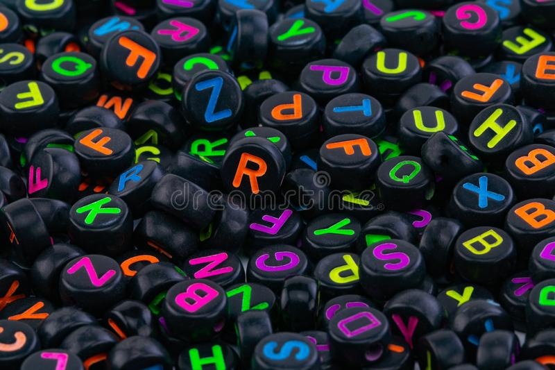 Black plastic beads with colored letters placed randomly.  stock photography