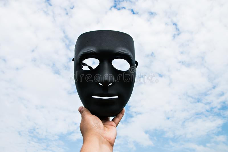 Black plastic mask on blue sky background in hand.  stock photo