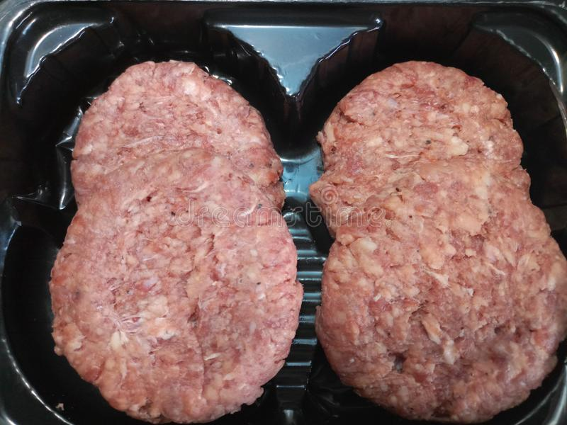 Four raw low fat beef burgers Close up royalty free stock photography