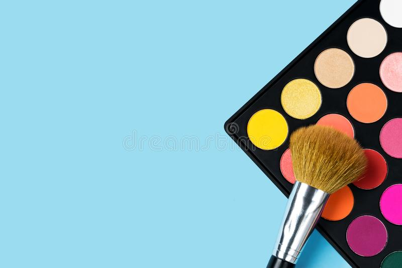 Black plastic palette of brightly coloured yellow, red, pink, orange eyeshadow and a large make-up brush laying on top of the royalty free stock photo