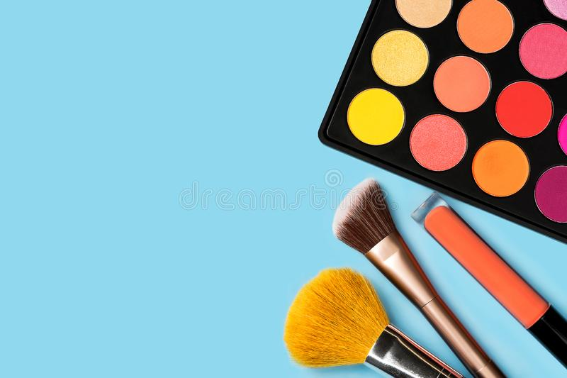 Black plastic palette of brightly coloured yellow, red, pink, orange eyeshadow, orange liquid lipgloss, and two make-up brushes royalty free stock photos