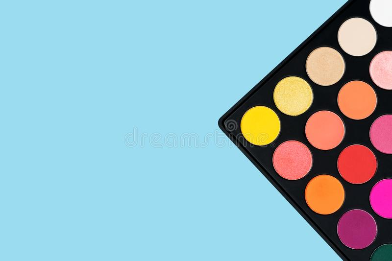 Black plastic palette of brightly coloured yellow, red, pink, orange eyeshadow placed in the corner of pastel baby blue background royalty free stock photos