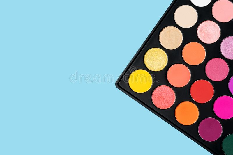 Black plastic palette of brightly coloured yellow, red, pink, orange eyeshadow placed in the corner of pastel baby blue background stock photo