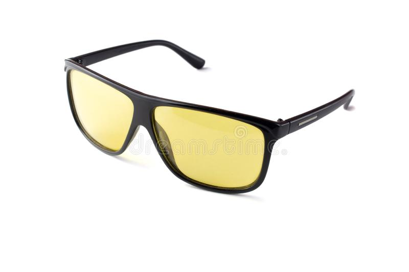 Black plastic sunglasses with yellow lenses on a white isolated background royalty free stock image