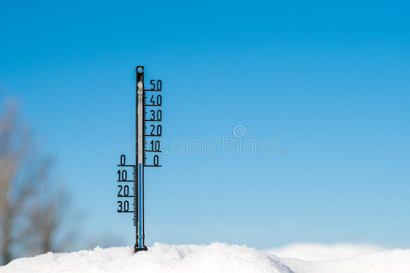 Black plastic thermometer in the snow with zero temperature, blue sky stock photos