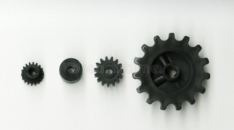 The black plastic toothed gears of different sizes on a white background. royalty free stock photos