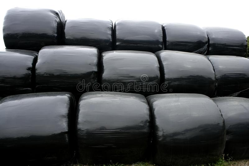 Black plastic wrap cover for cereal bales. Black plastic wrap cover for wheat cereal bales outdoor royalty free stock images