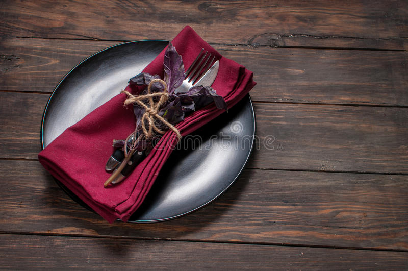 Black plate with fork,knife, napkin and basil on wooden table. royalty free stock images