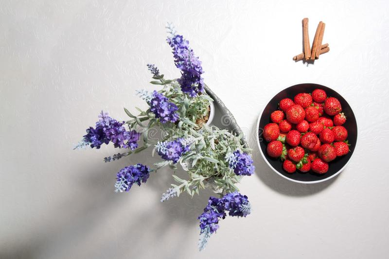 Black plate with juicy strawberry, top view. Fresh red berries in a black plate on a white table. Near pots with blue flowers and stock image