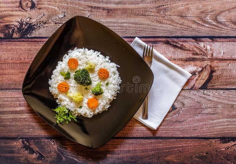 Black plate of rice with vegetable on wooden table. Close up royalty free stock photography