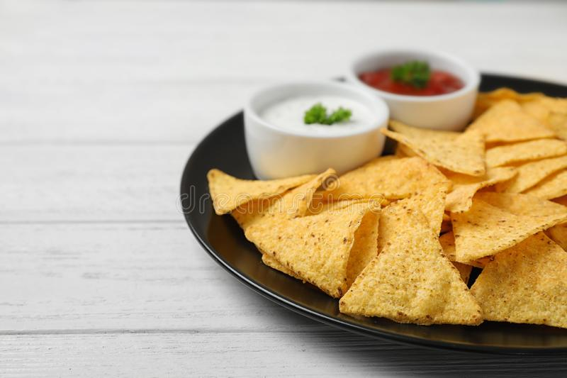 Black plate with tasty Mexican nachos chips and sauces on white wooden table, closeup royalty free stock images