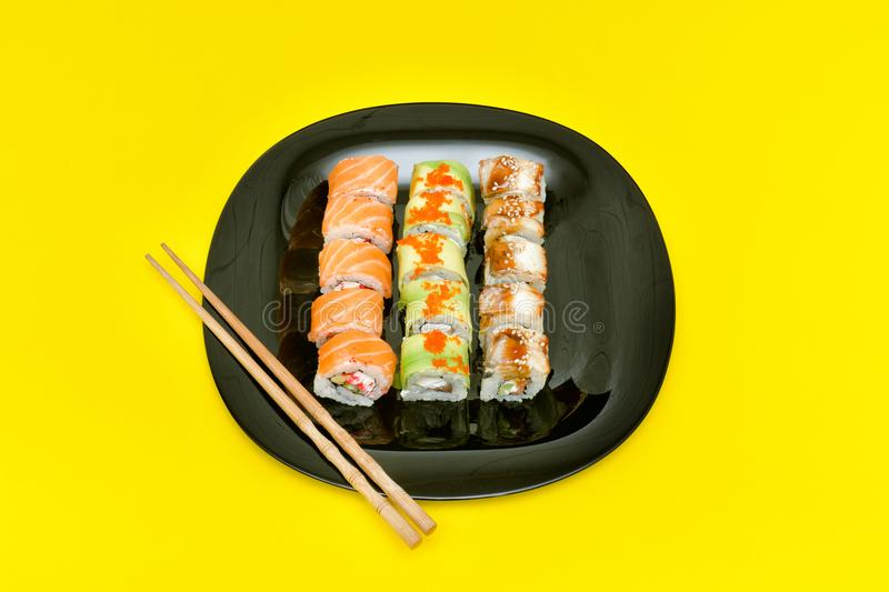 Black plate with various rolls on a yellow background. Top view stock photos