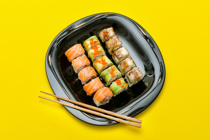 Black plate with various rolls on a yellow background. Top view royalty free stock photos