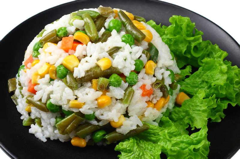 Black plate with white rice, green peas, canned corn kernels, cut green beans isolated on white background royalty free stock photo