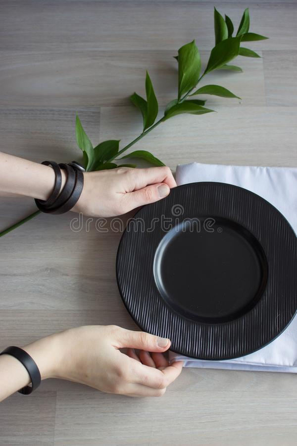 Black plate on white wooden background. With plant and napkin,top view. Empty plate for serving.  stock photography