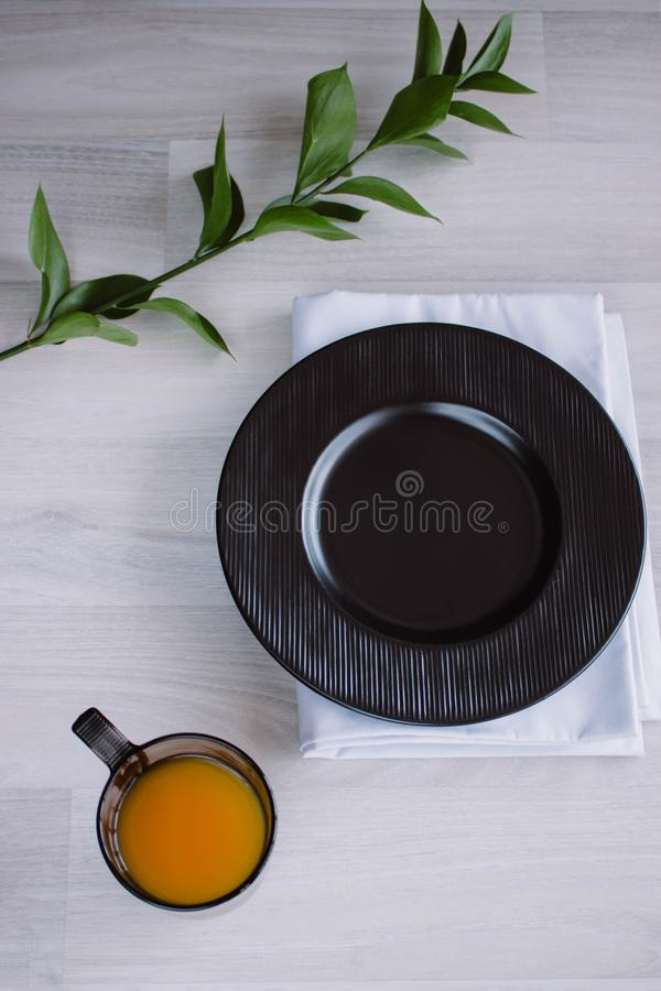 Black plate on white wooden background. With plant and napkin,top view. Empty plate for serving with orange juice.  stock photos